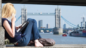 Girl reading with a view of Tower bridge